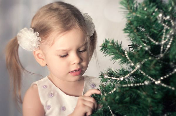 A little girg decorates a New Year tree