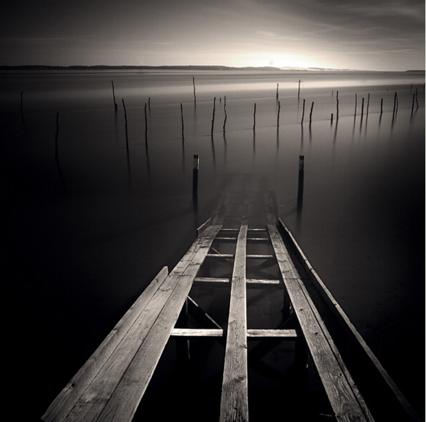 minimalist black and white photography: lake with a brocken bridge