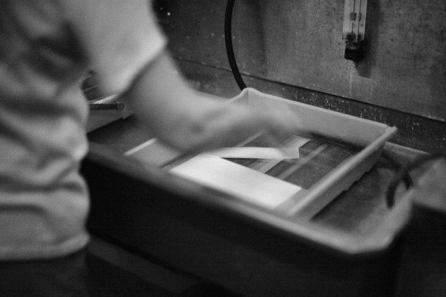 Developing prints in a chemical bath.  Photo by PHOTOarts/Magazine.