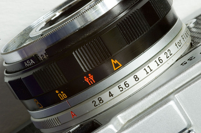 A focusing ring from an Olympus 35mm film camera.  We can see the ring as well as the ASA (ISO) setting and aperture selector.  Photo by George Rex.