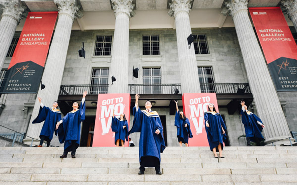 graduates with hats flying