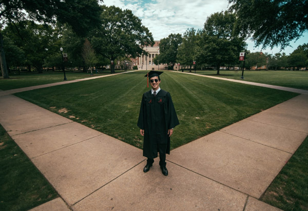 male graduate in front of building
